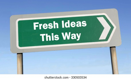Green road sign with the message of Fresh Ideas This Way concept against a blue sky background