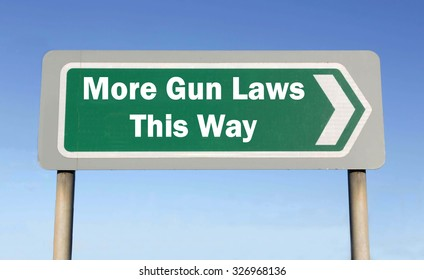 Green road sign with the message of More Gun Control Laws This Way concept against a blue sky background