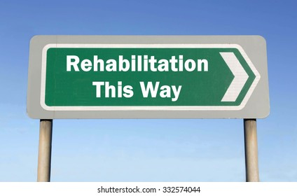 Green road sign with the message of Rehabilitation This Way concept against a blue sky background
