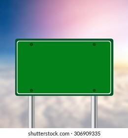 Green road sign on blurred sky and clouds.