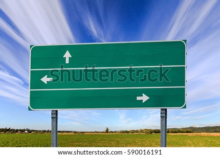 Green road sign with white arrows set against a blue sky.
