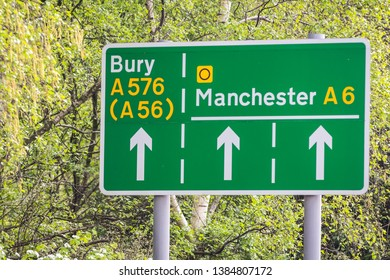 Green road signs on a leafy background showing directions to manchester and bury including the A6 A576 and A56.