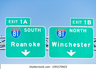 Green road signs in Virginia for exits 1A and 1B to Roanoke and Winchester along interstate highway 81 south and north isolated against blue sky
