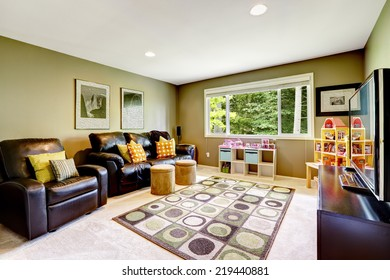 Green room with black leather couch and armchair. Playhouse for kids