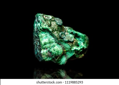 Green rough Malachite Mineral stone in front of black background, natural healing gemstone