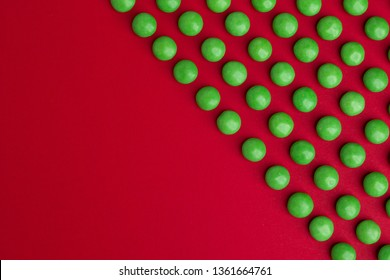 Green round chocolate candies on a red background with copyspace. Top view.