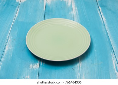 Green Round plate on blue wooden table with perspective side view