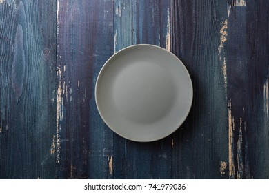 Green Round Plate on ocean blue wooden table background