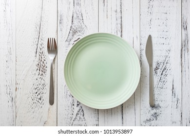 Green Round Plate with utensils on white wooden table background