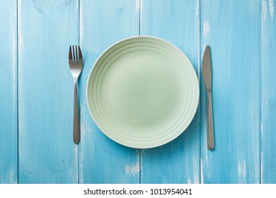 Green Round Plate with utensils on blue wooden table background