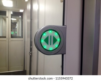 Green round touch button with arrows. Transparent door between carriages in intercity train