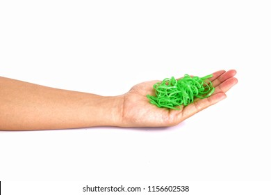 Green rubber band on palm, white background