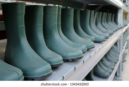 Green rubber boots in a long row. Classic work shoes for farmers and gardeners.