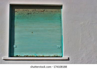 Green rusty metal window shutter on stucco wall
