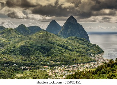 Green Saint Lucia landscape with Les Pitons mountains, seaside village and stormy sky