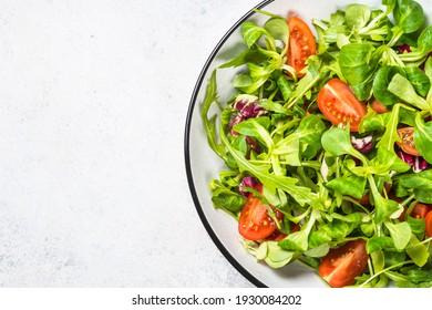 Green salad with arugula, lamb and tomatoes. Healthy vegan dish. Top view at white table.