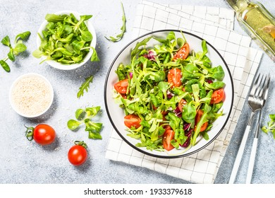 Green salad with arugula, lamb and tomatoes. Healthy vegan dish. Top view at white table.