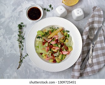 Green salad with avocado, baked salmon and dried tomatoes in a white plate on a gray concrete background. Top view.