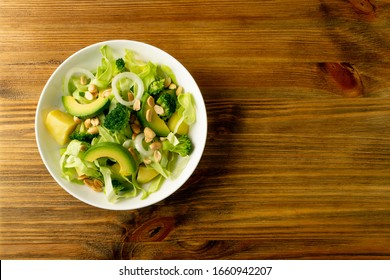 Green salad with avocado, cucumber, broccoli, potatoes and peanuts on white restaurant plate. Healthy organic vegan salat with sliced alligator pear or avocado pear top view with copy space - Shutterstock ID 1660942207
