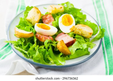 green salad with bacon and egg. style vintage. selective focus