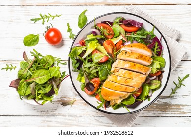 Green salad with baked chicken breast at white kitchen table. Healthy food, clean eating concept. Top view image.
