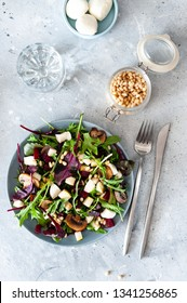 Green salad with beetroot, arugula, pieces of pear, mozzarella, mushrooms and pine nuts. On a gray background. Selective focus, the view from the top.