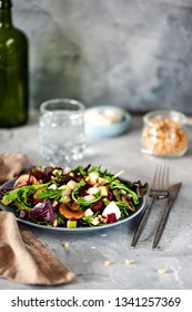 Green salad with beetroot, arugula, pieces of pear, mozzarella, mushrooms and pine nuts. On a gray background. Selective focus.