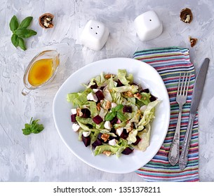 Green salad with boiled beetroot, feta and walnuts in a white plate on a gray concrete background. Seasoned with olive oil, grain mustard and vinegar. Healthy food. Top view.