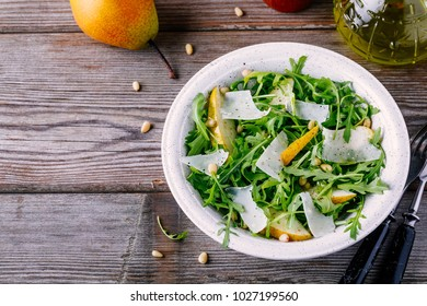 green salad bowl of arugula with pear, parmesan cheese and pine nuts on a wooden background