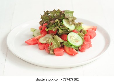 Green salad with cabbage, tomatoes and cucumber on the white plate