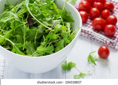 Green salad and cherry tomatoes on a white table