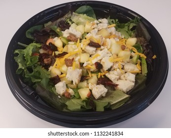 green salad with chicken, cheese, and fruit in black plastic container