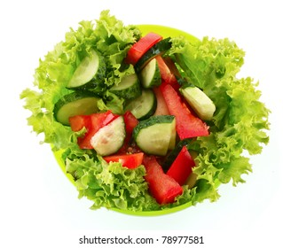 Green salad, cucumber and tomato in green plate isolated on white