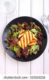 green salad with fried halloumi cheese on a black plate on a white background