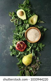 Green salad and fruits mix for salad with kale, young beetroot leaves, sprouts, pear, avocado, pomegranate, bowl of raw uncooked quinoa over dark texture surface. Top view, space. Food background.