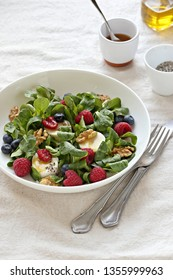Green salad with goat cheese, walnuts,  fresh berries and lemon honey dressing.