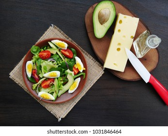 Green salad with healthy leaf vegetable, arugula, baby spinach, avocado, cherry tomatoes, red onions, hard boiled eggs on plate over woodeen table, Overhead view.