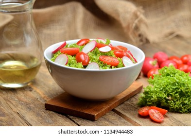 Green salad Lollo Biondo with tomatoes and radishes in a white bowl on wooden table, a pitcher of oil and jute fabric in the background