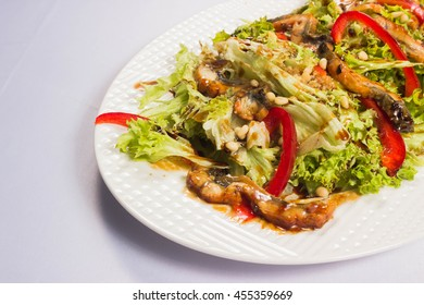 green salad made with sea eel, red peppers and nuts