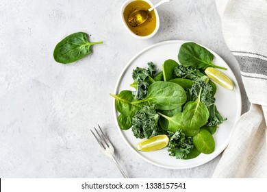 green salad of organic spinach and kale leaves with lemon juice and olive oil. diet menu concept, healthy detox food, selective focus, light background, food flat lay, salad recipe