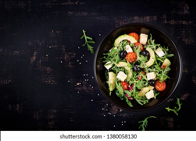 Green salad with sliced avocado, cherry tomatoes, black olives and cheese on wooden dark table. Healthy diet vegetarian summer vegetable salad. Table setting. Food concept. Top view.
