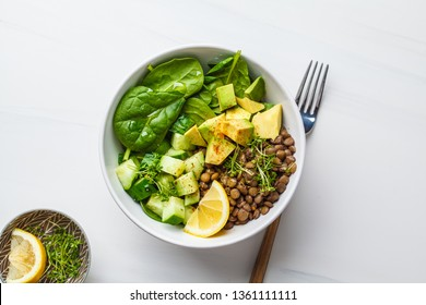 Green salad with spinach, lentils, avocado and cucumber. White background, top view.