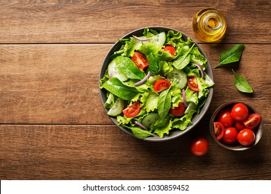 Green salad with tomato and fresh vegetables on a wooden background