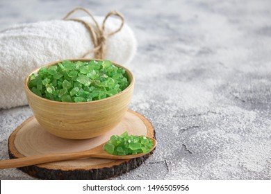 Green salt in wooden bowl and spoon, towel on concrete background. Spa, cosmetology, healthcare concept. Close-up, soft focus, copy space