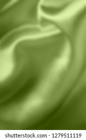 Green satin fabric, draping with soft folds. Blurred background.