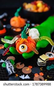 Main verte effrayante tenant des bonbons d'Halloween