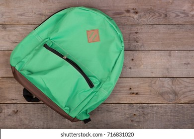 Green school backpack on brown wooden table. Top view