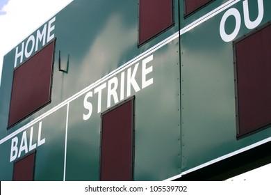 A green scoreboard in the outfield of a baseball field