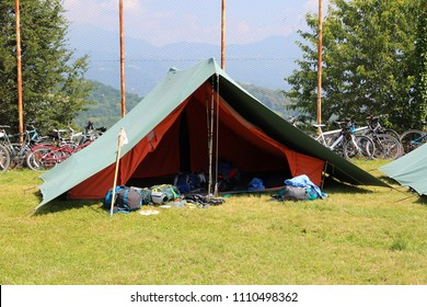 green scout tent with backpacks out and with bikes in the background
