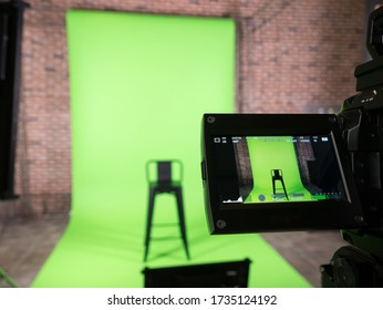 green screen backdrop and black chair with lcd display screen on a High Definition TV camera ,  in studio at TV station. Checking before on air.